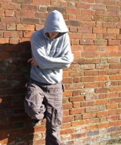 http://images.wisegeek.com/man-in-hooded-sweater-leaning-against-brick-wall.jpg