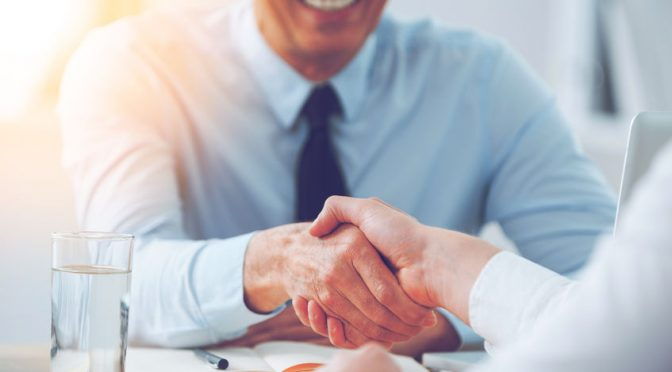 54625309 - good deal. close-up of two business people shaking hands while sitting at the working place