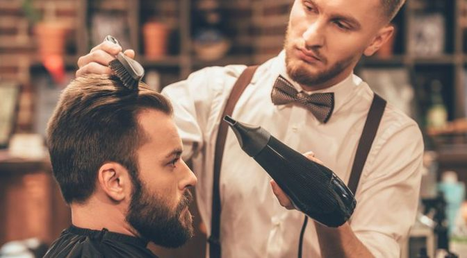 51259661 - new hairstyle. side view of young bearded man getting groomed at hairdresser with hair dryer while sitting in chair at barbershop