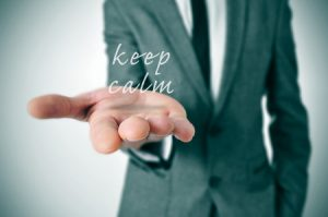 27715526 - man wearing a suit with the text keep calm in his hand