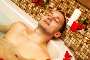 17851940 - young man in spa. romantic jacuzzi with flowers and candles
