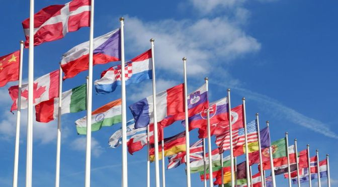 46930062 - world flags blowing in the wind on the cloudy sky background