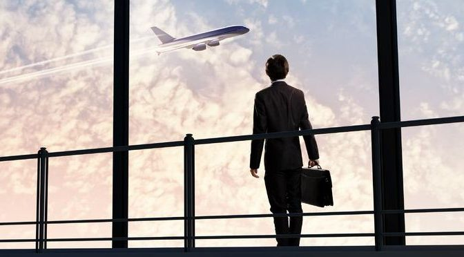 21552814 - image of businessman at airport looking at airplane taking off